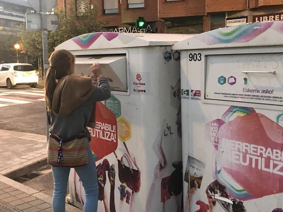 Una chica deposita ropa en el contenedor blanco de la reutilización de Koopera